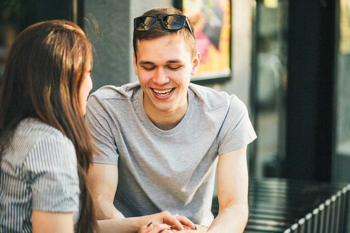 Fröhlicher junger Mann mit Partnerin